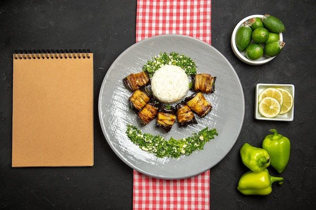 Vista dall'alto deliziosi involtini di melanzane piatto cucinato con riso sulla superficie scura cucinando olio vegetale di riso