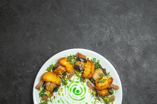 トップビューダークデスクディッシュミールディナーロールポテト野菜のプレートの中にベイクドポテトが入ったおいしいナスロール