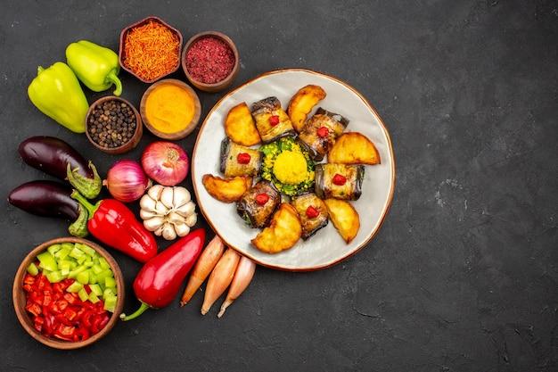 어두운 배경 접시에 감자와 신선한 야채를 곁들인 맛있는 가지 롤