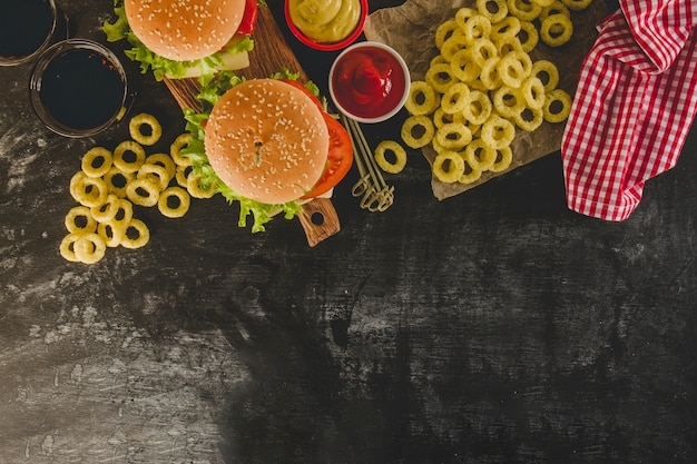 Top view of delicious fast food menu with onion rings