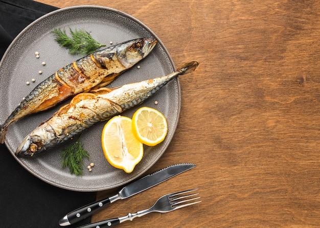 Вид сверху вкусной рыбы на тарелке