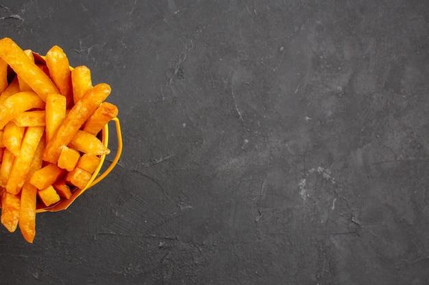 Vista dall'alto deliziose patatine fritte all'interno del pacchetto sul pasto di hamburger piatto di patate fast-food sfondo scuro dark