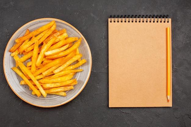 Vista dall'alto deliziose patatine fritte all'interno del piatto sullo sfondo scuro pasto di patate piatto sandwich hamburger fast-food