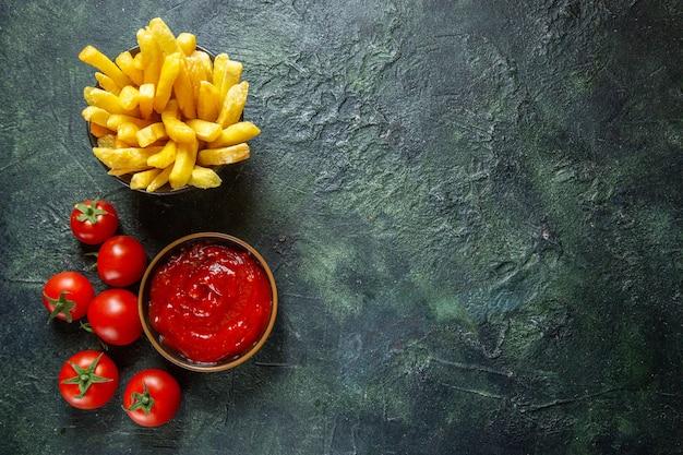 Vista dall'alto deliziose patatine fritte con pomodorini sulla superficie scura