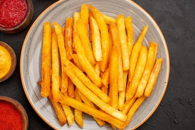 Vista dall'alto deliziose patatine fritte con salse sullo sfondo scuro fast food piatto di patate hamburger
