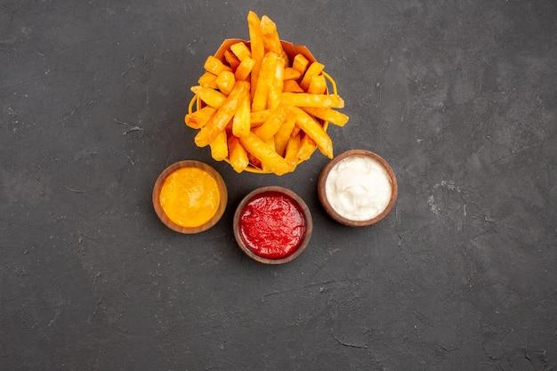 Vista dall'alto deliziose patatine fritte con condimenti su sfondo scuro hamburger fast-food piatto di patate