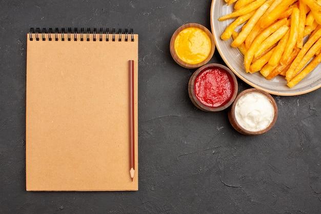 Vista dall'alto deliziose patatine fritte con condimenti su sfondo scuro piatto di patate fast-food hamburger pasto