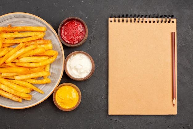 Vista dall'alto deliziose patatine fritte con condimenti su sfondo scuro piatto di hamburger fast-food di patate