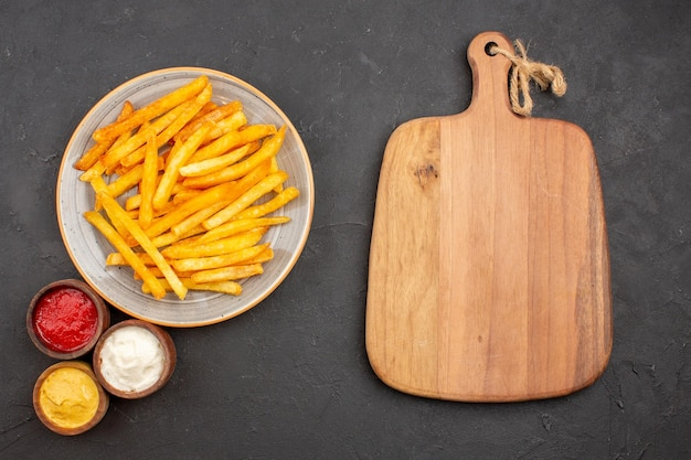 Top view delicious french fries with seasonings on dark background potato meal dish burger fast-food