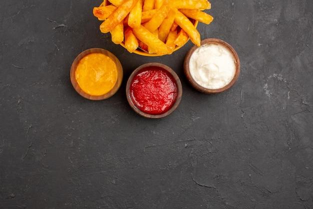Vista dall'alto deliziose patatine fritte con condimenti su piatto di patate fast-food hamburger da scrivania scuro