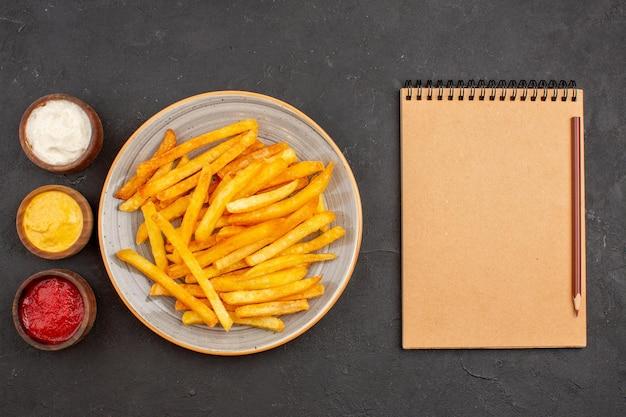 Vista dall'alto deliziose patatine fritte con condimenti su un piatto di fast food con hamburger di patate scure da scrivania