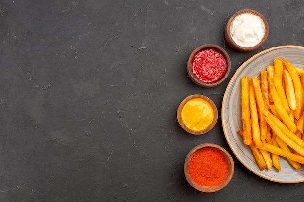 어두운 배경 패스트 푸드 식사 감자 요리 햄버거에 조미료와 상위 뷰 맛있는 감자 튀김