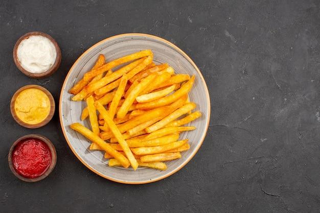 Вид сверху вкусный картофель фри с приправами на темном фоне картофельная еда гамбургер блюдо быстрого питания