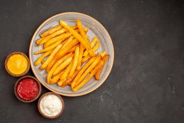 어두운 책상 접시 감자 식사 패스트 푸드 햄버거에 조미료와 상위 뷰 맛있는 감자 튀김