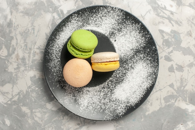 Top view delicious french macarons inside plate on white background cake biscuit sugar bake sweet pie