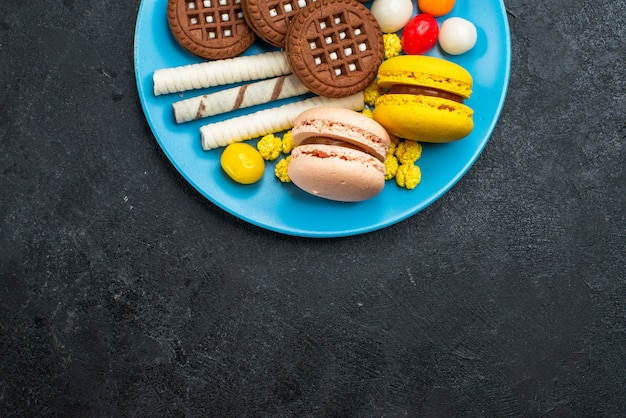 Top view delicious french macarons with candies and chocolate cookies on dark grey background biscuit sugar cake sweet bake cookies