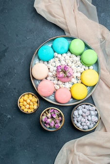 Top view delicious french macarons with candies on grey space