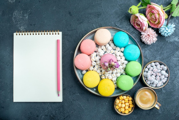 Top view delicious french macarons with candies inside tray on dark desk
