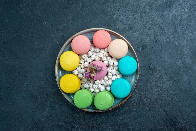 Top view delicious french macarons with candies inside tray on dark space