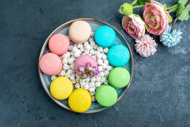 Vista dall'alto deliziosi macarons francesi con caramelle all'interno del vassoio nello spazio buio