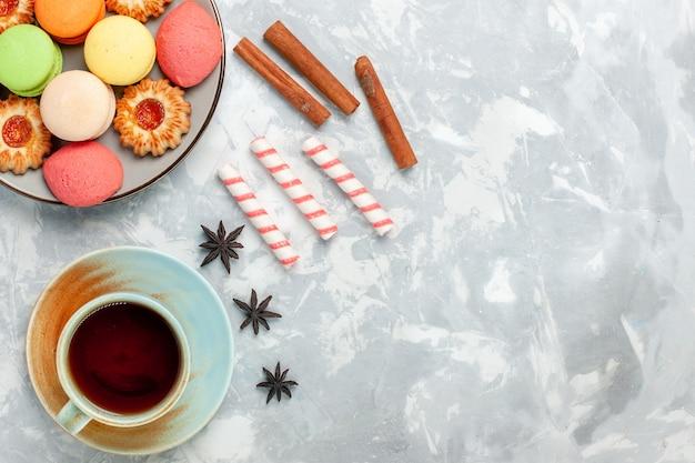 トップビュークッキーシナモンとライトホワイトの背景にお茶とおいしいフレンチマカロン焼きケーキビスケット砂糖甘い写真