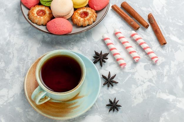 トップビュークッキーシナモンと明るい白い机の上のお茶とおいしいフランスのマカロン焼きケーキビスケット砂糖甘い写真
