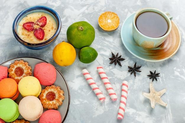 トップビュークッキーデザートと明るい白い机の上のお茶とおいしいフランスのマカロン焼きケーキビスケット砂糖甘い写真