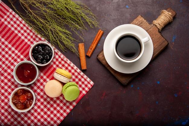 トップビューフルーツジャムと暗い背景の上のコーヒーのおいしいフレンチマカロン甘いフルーツマーマレードケーキビスケット甘い砂糖
