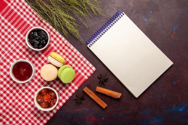Vista dall'alto deliziosi macarons francesi con marmellate di frutta sulla scrivania scura marmellata dolce tè torta biscotto dolce