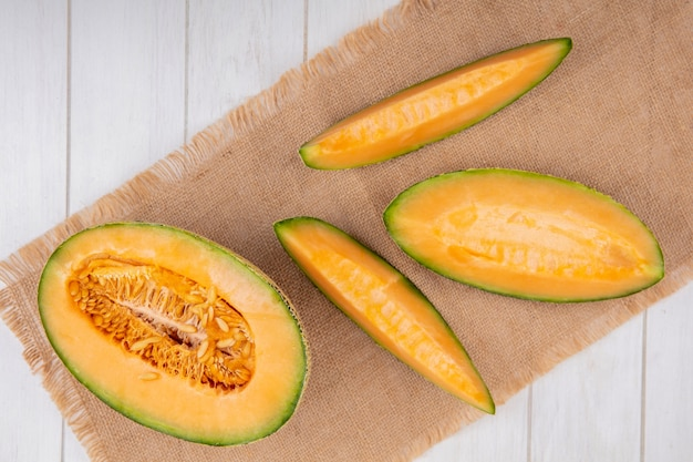 Top view of delicious and fresh melon with slices on sack cloth on white wood
