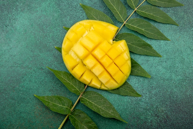 Top view of delicious and fresh sliced mango with leaf on green