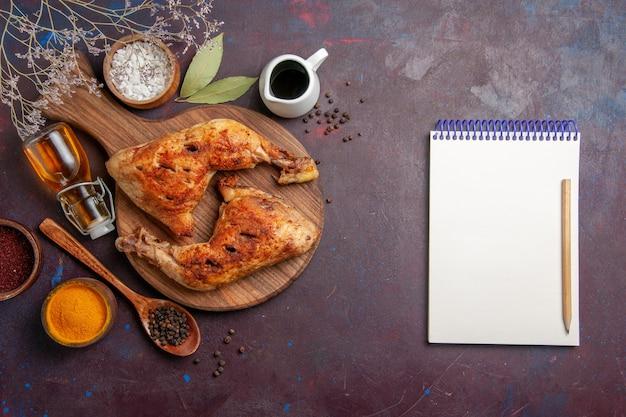 Вид сверху вкусной жареной курицы с разными приправами на темном пространстве