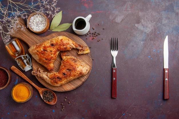 Вид сверху вкусной жареной курицы с разными приправами на темном столе