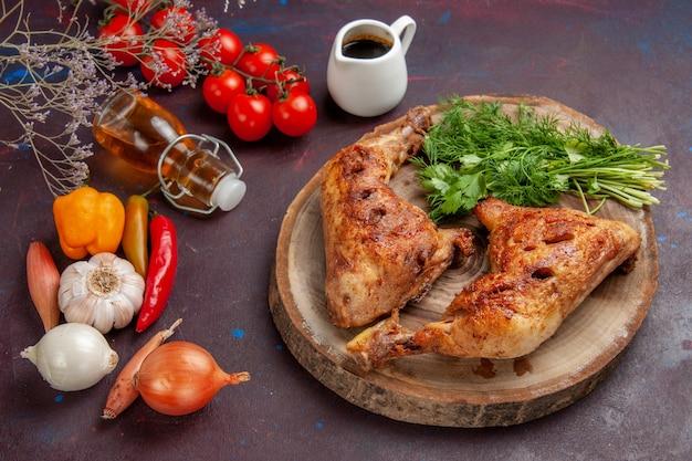 Вид сверху вкусной жареной курицы со свежими овощами и зеленью на темном столе