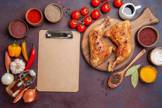 Вид сверху вкусной жареной курицы с приправами и овощами на темном пространстве