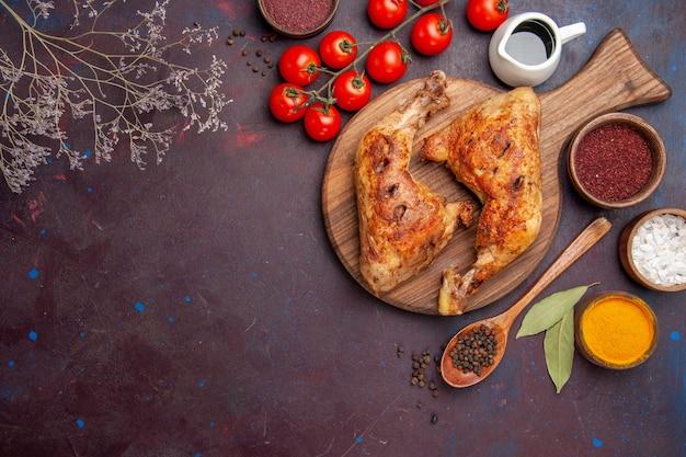 Вид сверху вкусной жареной курицы с приправами и овощами на темном столе