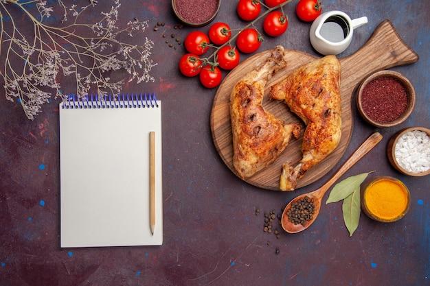 Вид сверху вкусной жареной курицы с приправами и овощами на темном полу блюдо из мяса и курицы