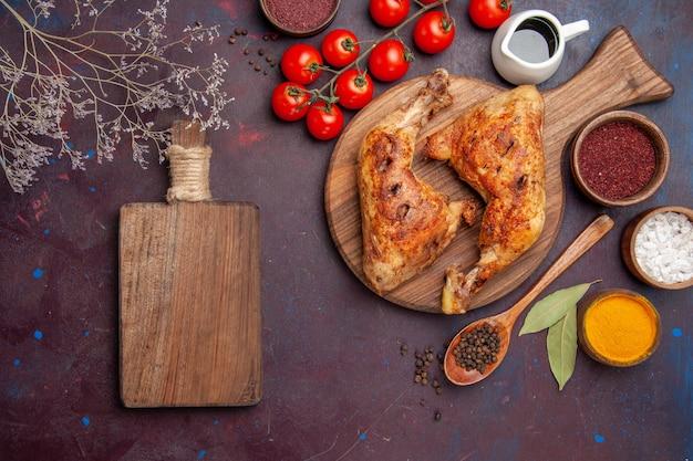어두운 보라색 공간에 조미료와 야채와 함께 상위 뷰 맛있는 프라이드 치킨