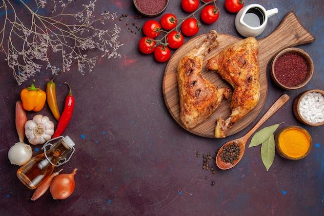 어두운 공간에 조미료와 야채와 함께 상위 뷰 맛있는 프라이드 치킨