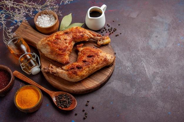 Вид сверху вкусной жареной курицы с приправами на темном пространстве