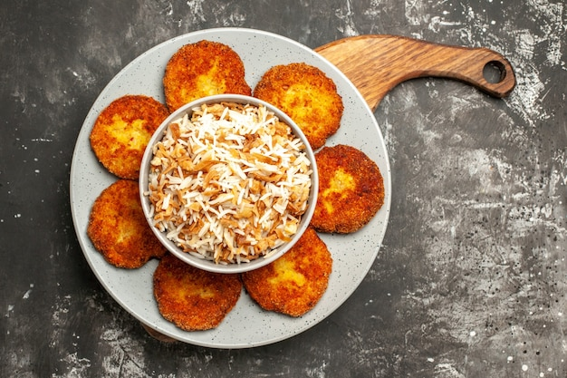 Top view delicious fried cutlets with cooked rice on a dark surface dish meat rissole