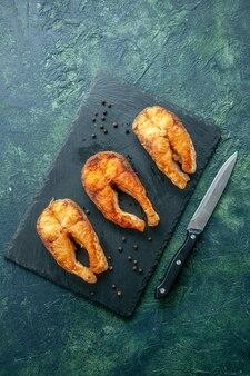 Vista dall'alto delizioso pesce fritto sulla superficie scura piatto insalata di frutti di mare frittura di carne pepe di mare cucina pasto