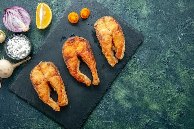 Vista dall'alto delizioso pesce fritto sulla superficie scura piatto insalata di frutti di mare carne di mare pepe di mare cibo acqua pasto