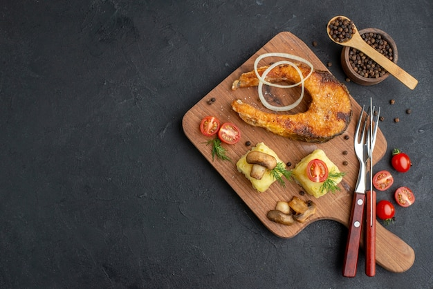 Top view of delicious fried fish and mushrooms tomatoes greens on wooden cutting board cutlery set pepper on black surface