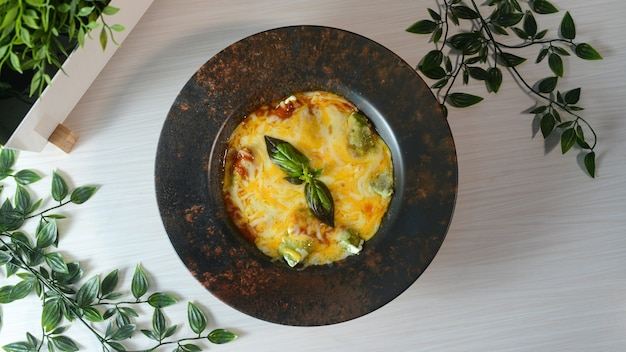Top view of delicious frittata on a black plate on a wooden surface