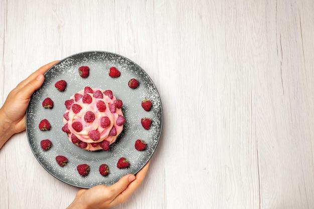 上面図白い背景に新鮮なラズベリーとおいしいフルーツケーキクリームデザート甘いクリームティーデザートビスケットケーキパイ