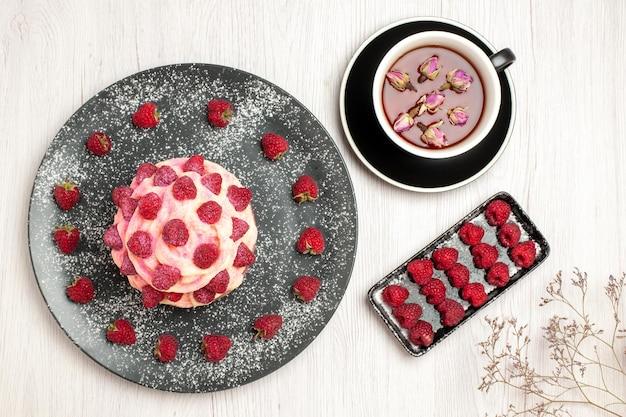 上面図白い背景にラズベリーとお茶とおいしいフルーツケーキクリームデザート甘いクリームティーデザートビスケットケーキパイ
