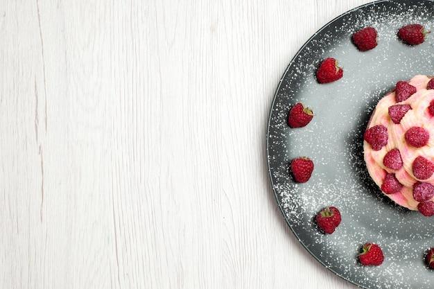 上面図白い背景にラズベリーとおいしいフルーツケーキクリームデザートクリームデザートビスケット甘いケーキパイクッキー