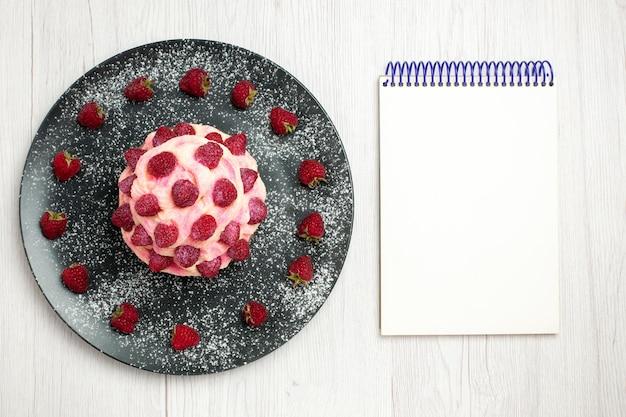 上面図白い背景にラズベリーとおいしいフルーツケーキクリームデザートクリームデザートビスケット甘いケーキパイティー