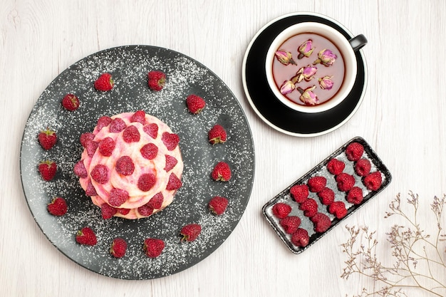 Top view delicious fruit cake cream dessert with raspberries and tea on white background sweet cream tea dessert biscuit cake pie